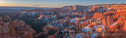 Sunrise at Bryce Amphitheater with warm glow on the hoodoos and snow dotting the canyon walls, Bryce Canyon National Park.