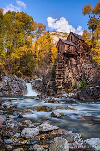 The historic powerhouse Crystal Mill on the Crystal River is captured with autumn colors on the aspen leaves and warm evening light illuminating the scene.