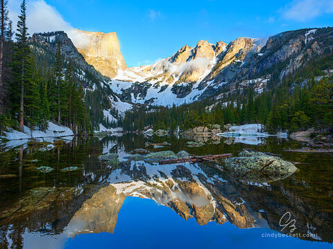 A calm and glass-like Dream Lake reflects Hallett Peak and Flat Top mountain on an early summer morning.