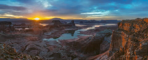 Sun beams breaking over the distant buttes and mesas of Glen Canyon cast warm light on the scene around Gunsight Butte and the waters of Lake Powell.
