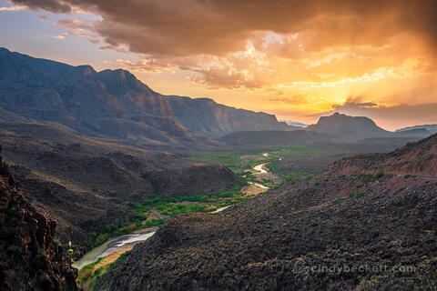Sun light spreads into rays through colorful thunderstorm clouds over the Rio Grande river canyon as it winds its way between Texas and Mexico from the Big Hill