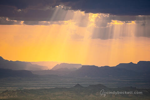 Sun rays shine through thunderstorm clouds as warm afternoon light bathes the scene over Santa Elena Canyon and the Burro Mesa of Big Bend National Park.