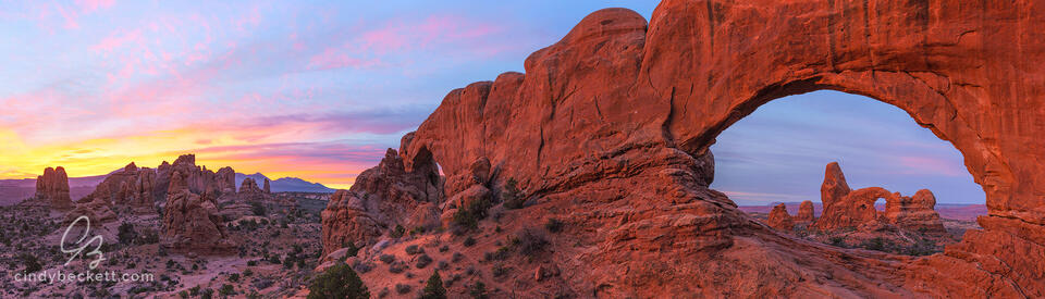 Panorama of Turret Arch through the north window with the south window and other hoodoos in the scene with colorful dawn light and clouds.