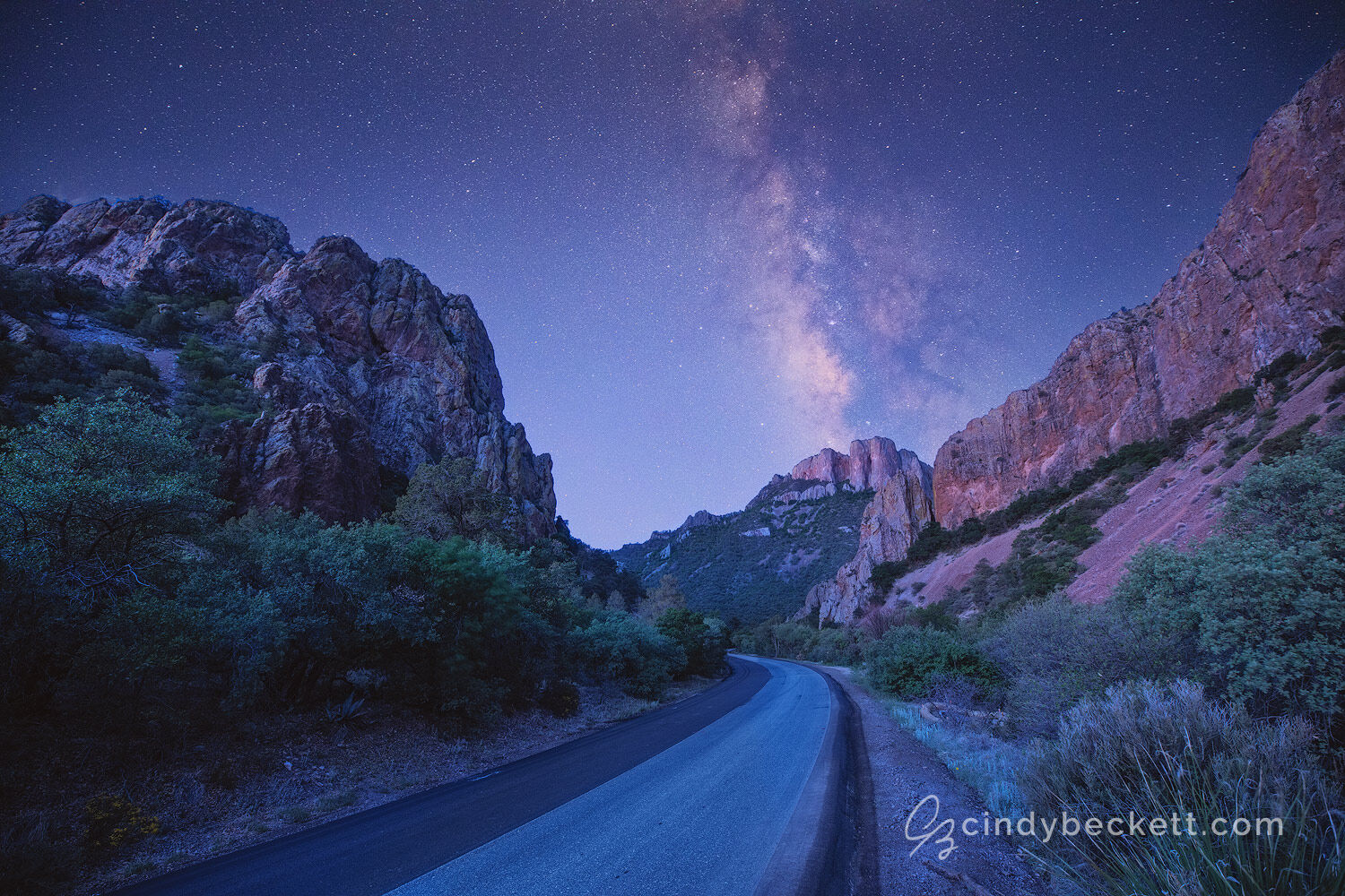 The Milky Way rises above the mountain peaks and canyon walls of the road leading into Chisos Basin in Big Bend National Park.