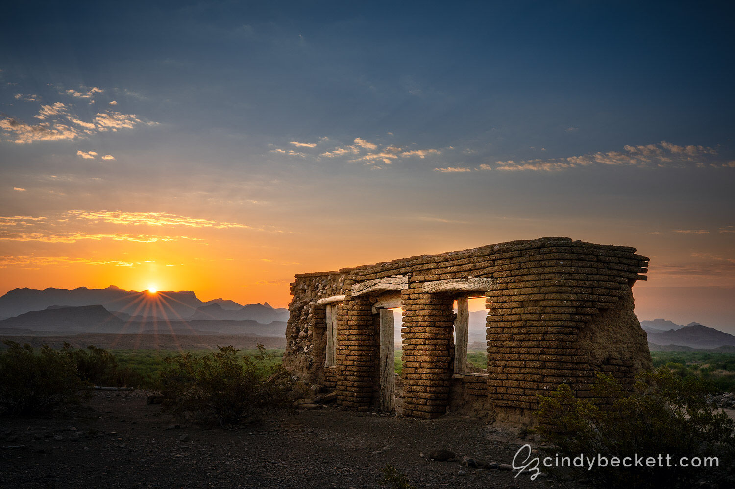 The sun rises over the distant mountains of the Chisos Basin area with the historic adobe structure known as Dorgan farm sitting on the foreground mesa.