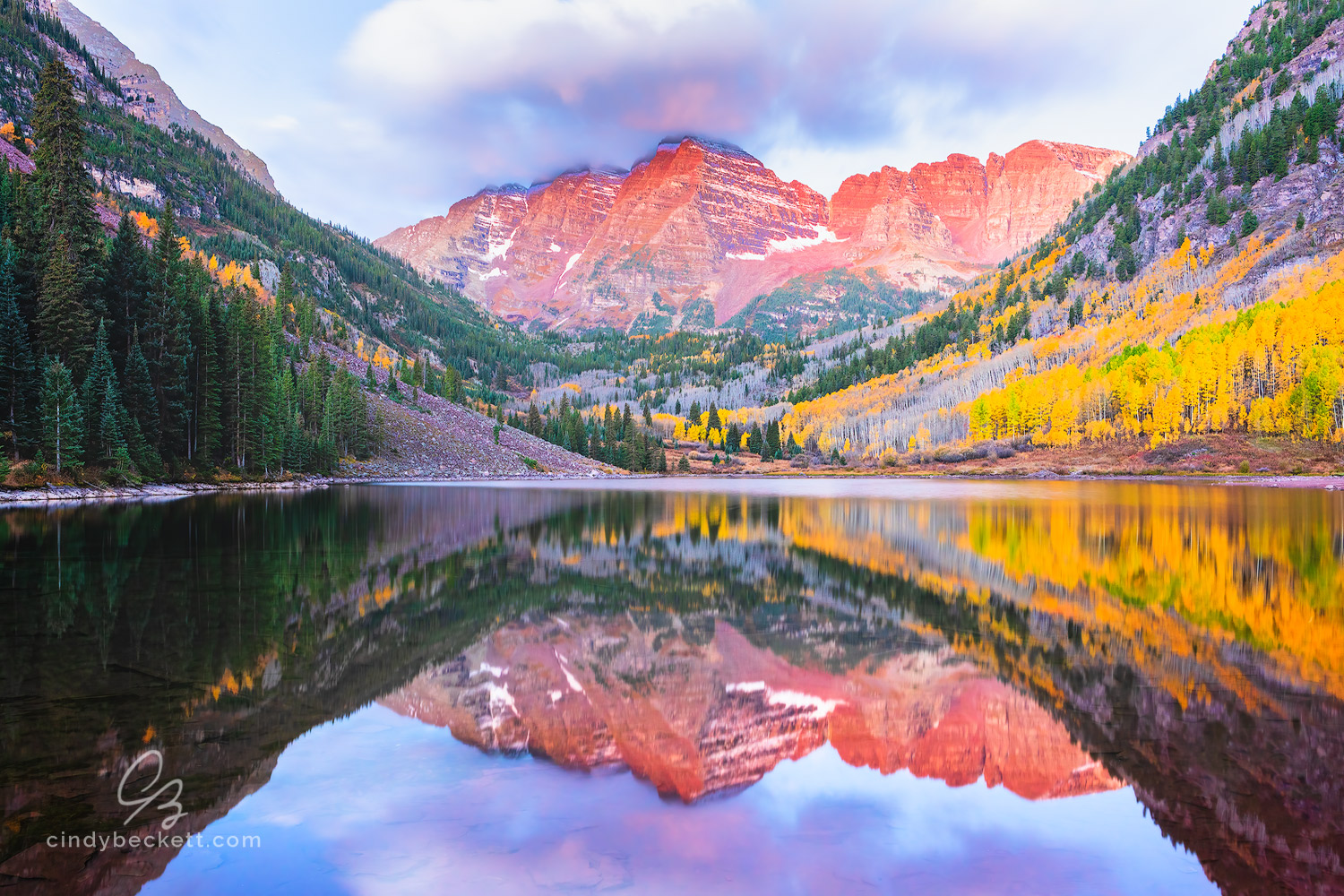 Dawn light over Maroon Bells mountain peaks with glass-like reflections in Maroon lake under colorful cloudy sky and with aspen leaves turning to fall colors.