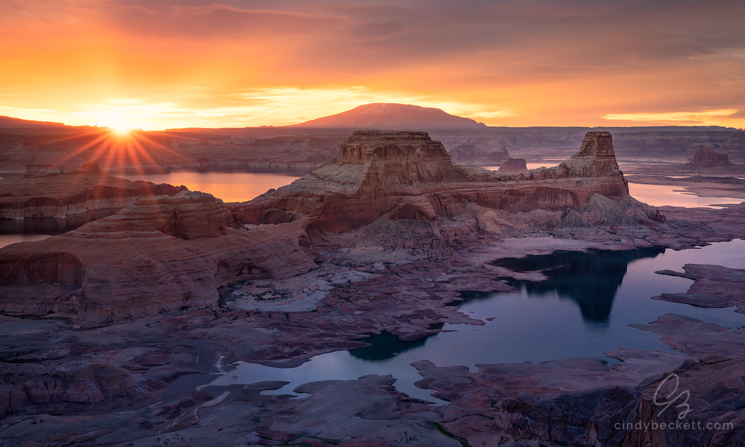 A cloudy and colorful sunrise scene over red rock canyon walls and formations surrounded by the waters of Lake Powell.